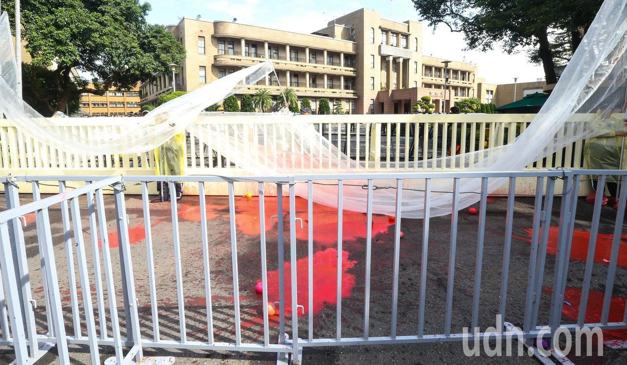 各勞團工會代表今天上午齊聚行政院前抗議,最後向行政院大門投擲紅色水球,現場一片狼...