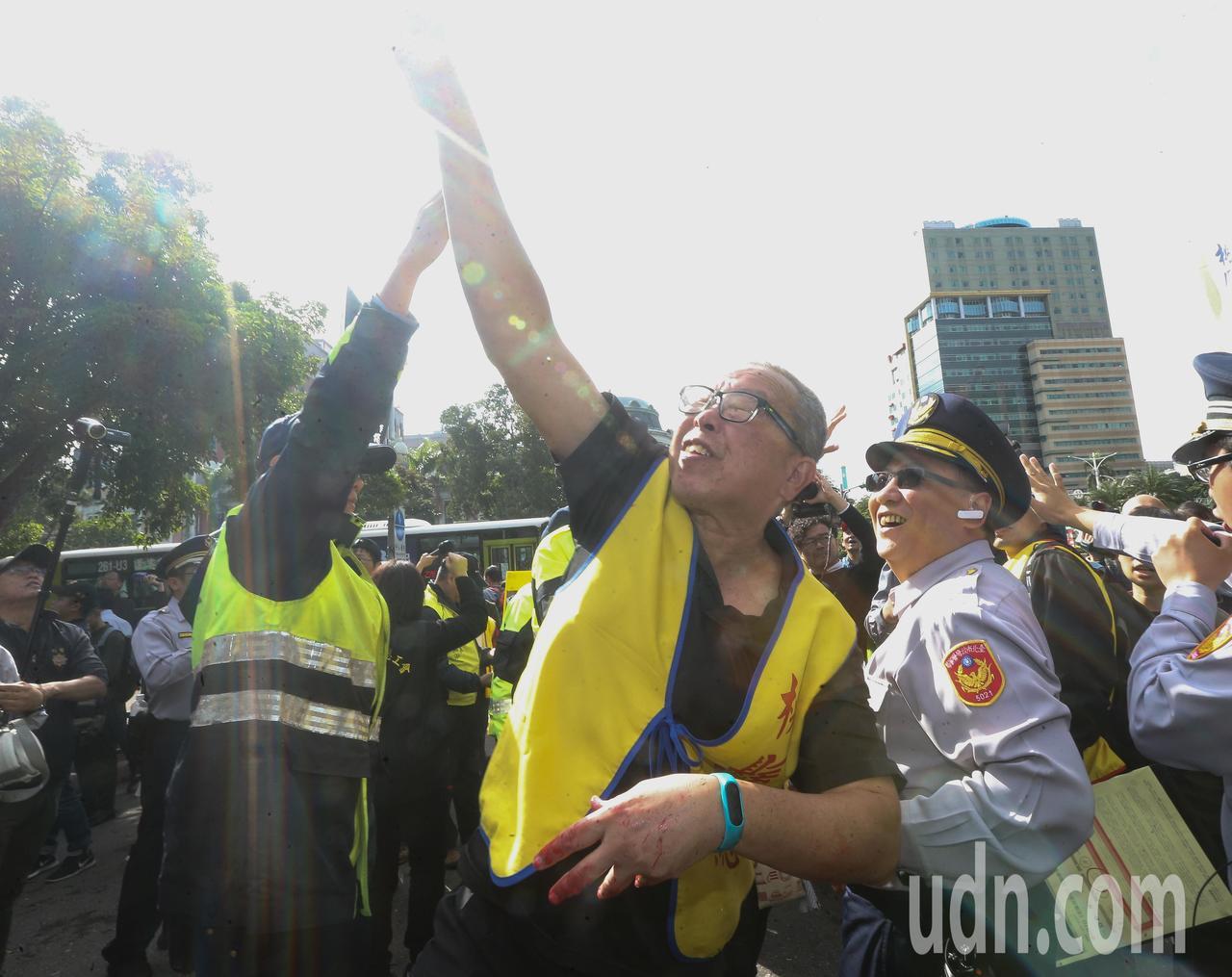 各勞團工會代表今天上午齊聚行政院前抗議,最後朝著行政院大門投擲紅色水球,警方則在...