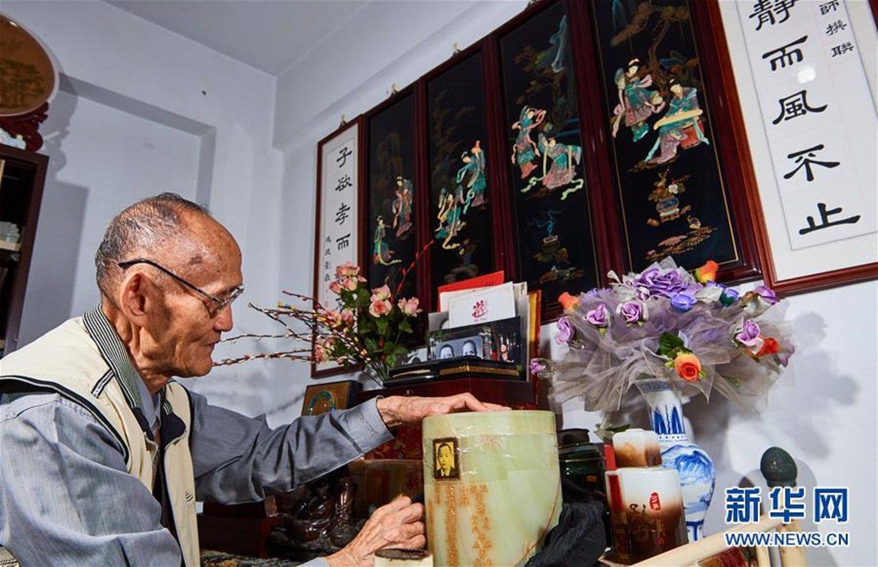 高秉涵在擦拭一位老兵的骨灰罈。新華社