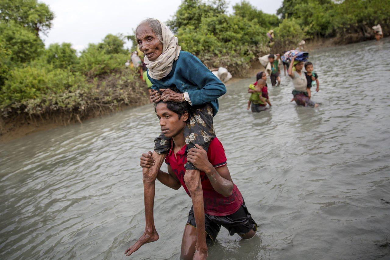 在穿越緬甸邊界進入孟加拉後,1名年輕洛興雅男子背著1名老婦涉水尋找棲身之地。( ...