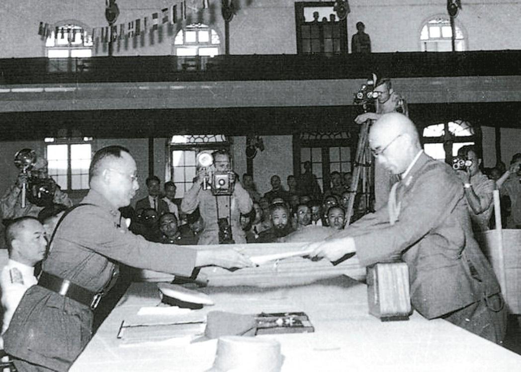 圖為1945年9月9日的南京受降典禮,日本駐華派遣軍總司令岡村寧次簽署降書後,由...