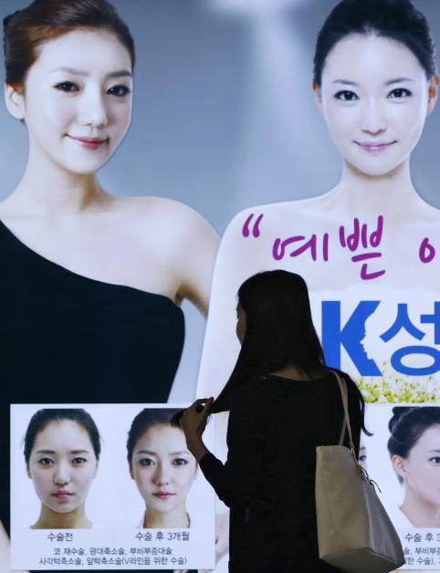一名女子佇足端詳首爾地鐵站內的整型廣告。歐新社