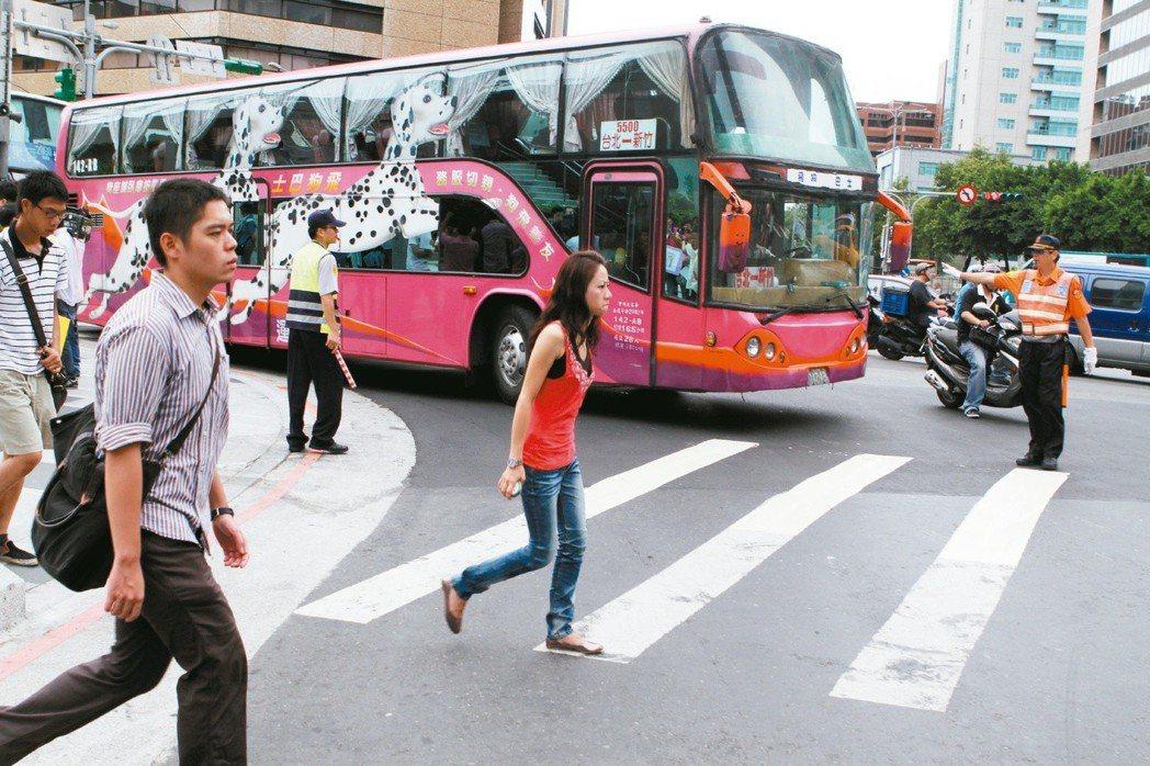 行人過馬路時要注意路口轉彎大型車,避免進入內輪差範圍,釀生危險。 本報資料照片