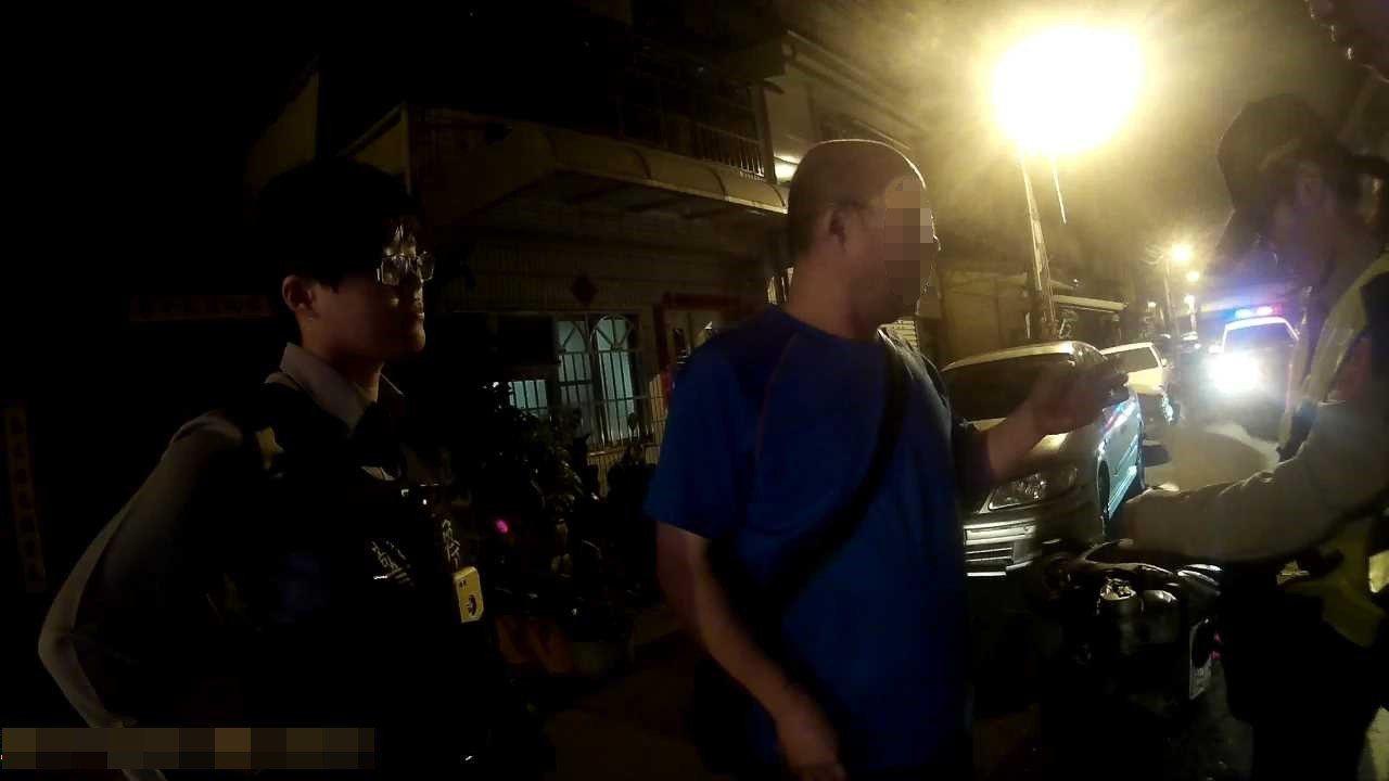 陳男騎摩托車酒駕自撞停在路旁汽車,警方到場,陳男(中)拒絕酒測。記者劉星君/翻攝