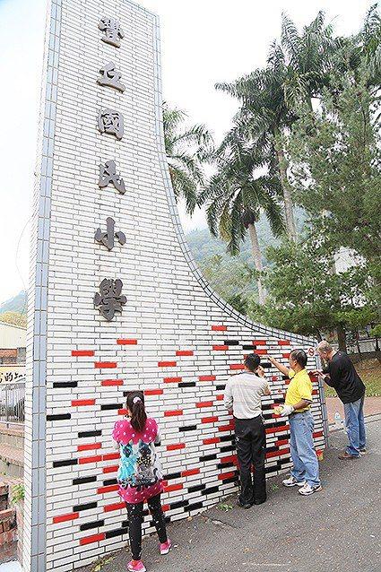 畫家們在豐丘國小幾個大字下的白瓷磚,以自由方式彩繪黑與紅色,增加活潑韻致。 曹松...