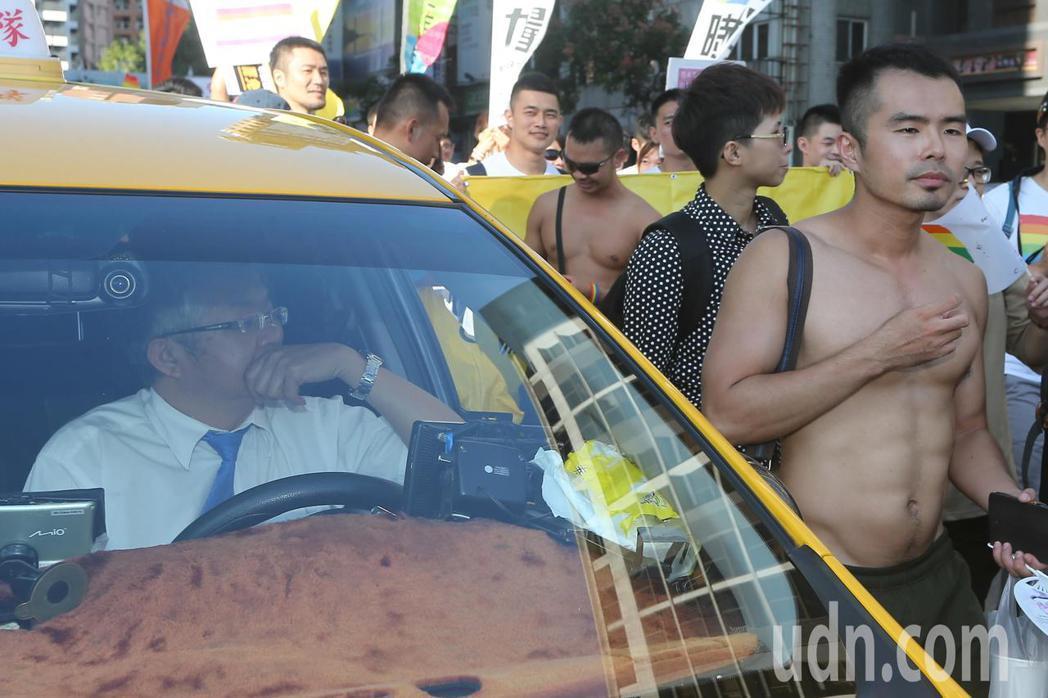 同志大遊行11月18日在台中登場,有計程車司機等候時,好奇在車內觀看遊行人潮。記...