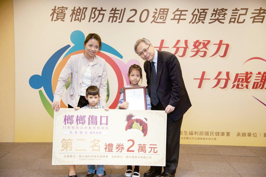 國健署署長王英偉(右起),頒獎給得主康茞芯,媽媽和弟弟一起上台領獎。