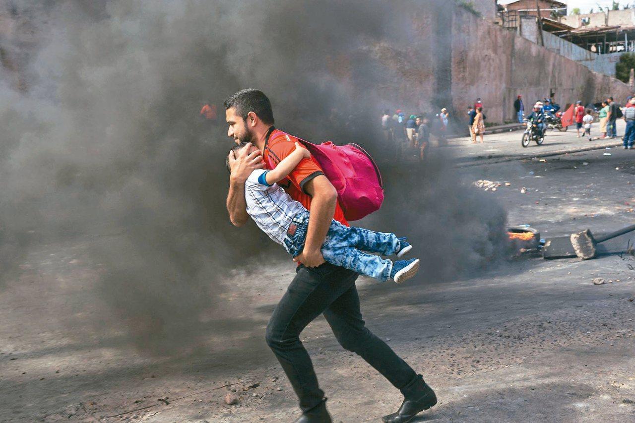 德古西加巴群眾示威;一位父親抱稚子穿越冒著黑煙的街道。 (美聯社)