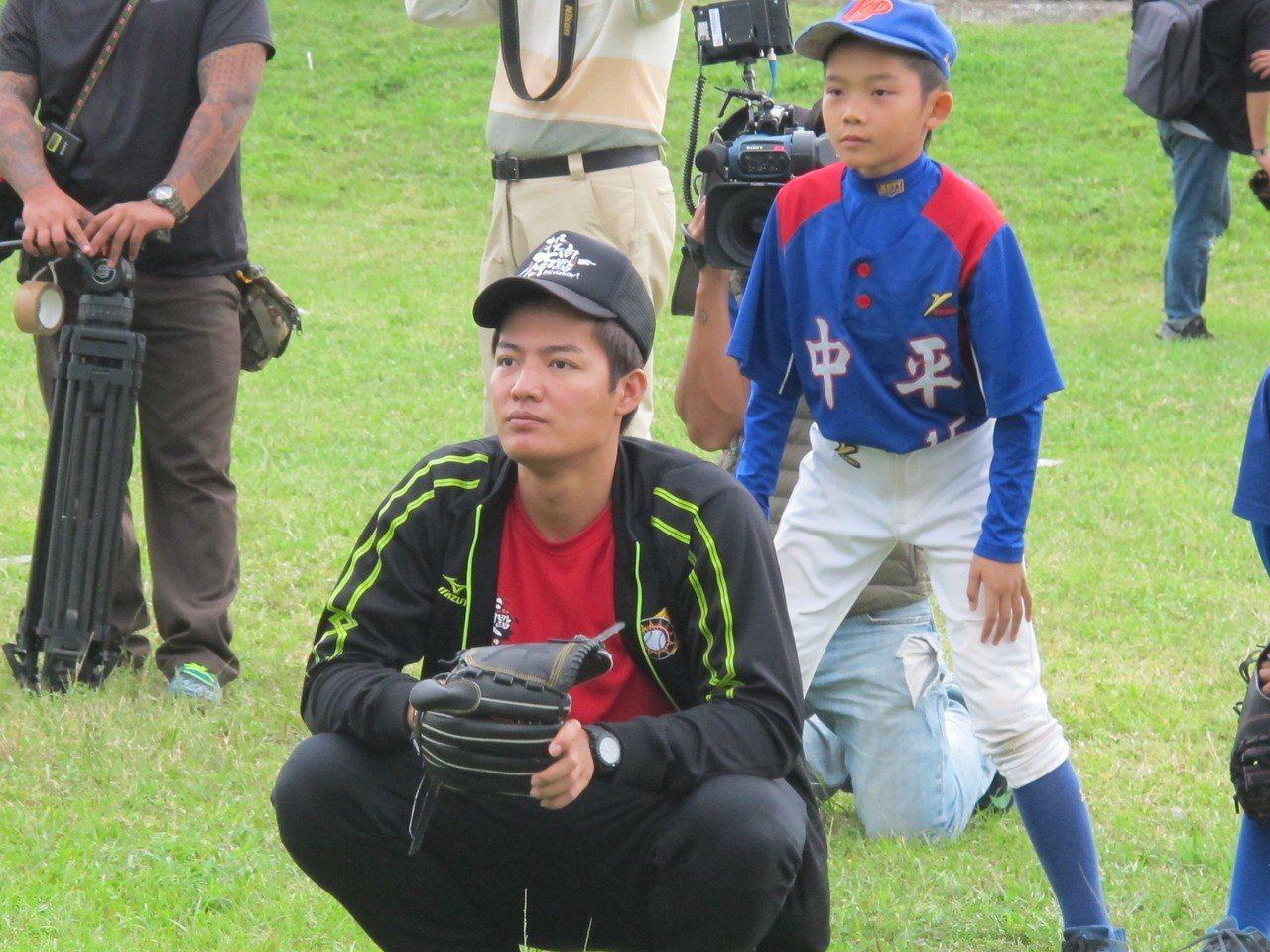 旅美投手王維中在關懷盃戴上手套,親自蹲捕小球員投球。 記者吳敏欣/攝影
