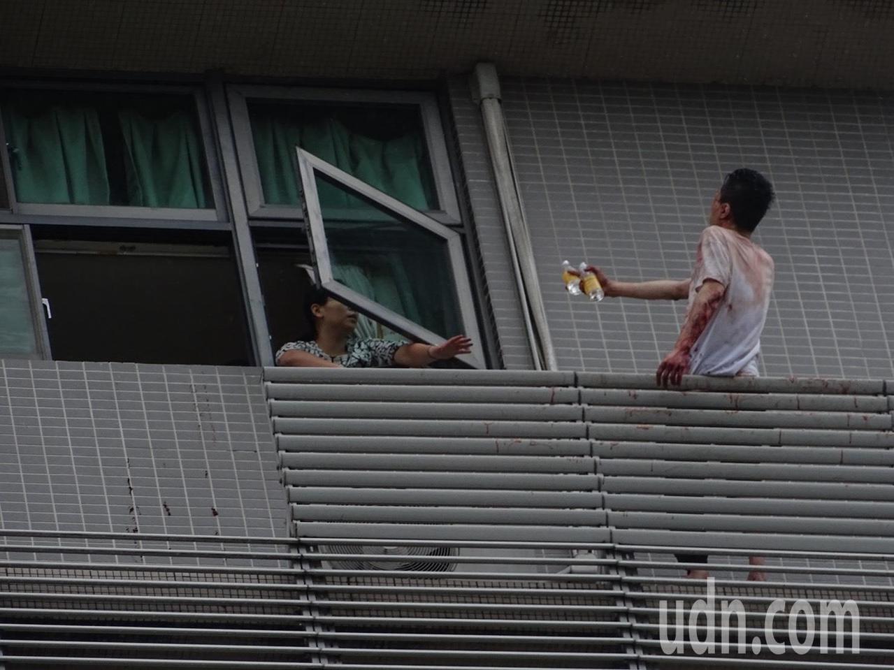 新店一名男子上午站在大樓陽台情緒不穩疑欲自殺,屋內有人遞水,勸他進屋。記者江孟謙...