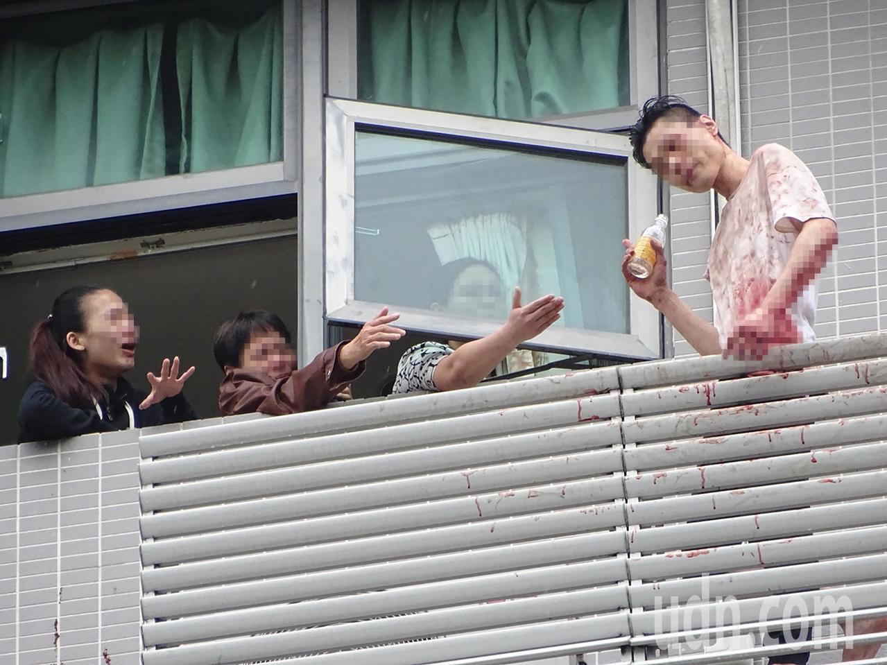 新店一名男子上午站在大樓陽台情緒不穩疑欲自殺,家屬哭紅了眼,勸他進屋。記者江孟謙...