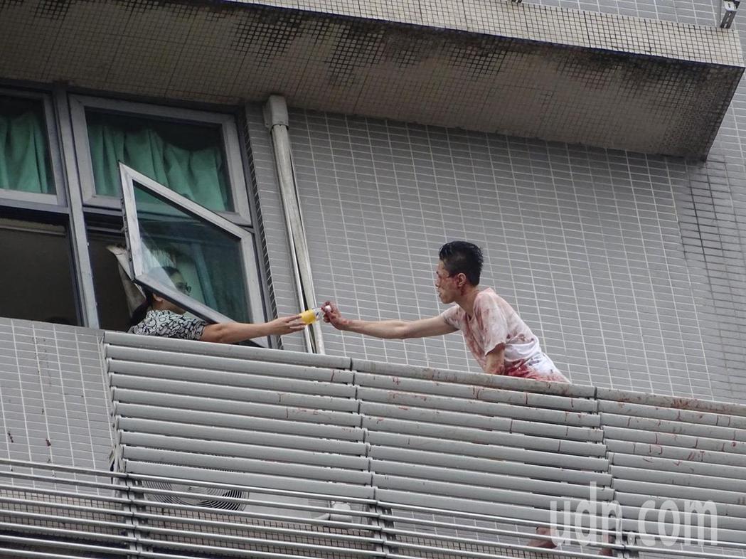 新店一名男子上午站在大樓陽台情緒不穩疑欲自殺,屋內有人遞水給他緩和情緒。記者江孟...