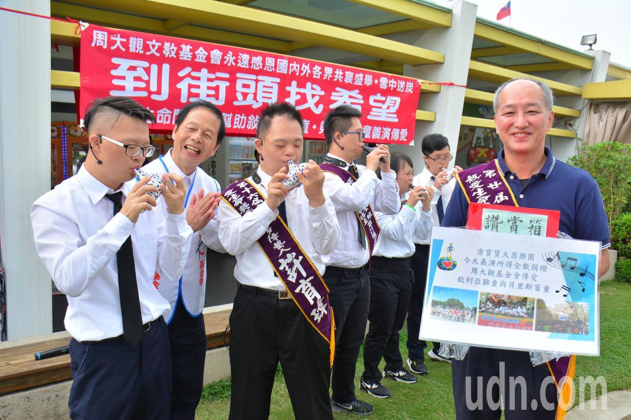 唐寶寶大器樂團團長林啟通(右)14年來指導喜憨兒,獲得周大觀文教基金會2017年...