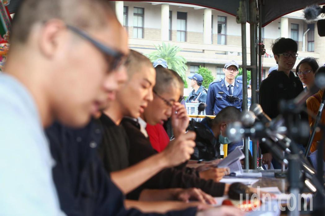 網友今天下午在行政院前舉辦「過勞大悲功德大法會-集誦勞基法經」活動,現場誦經、剃...