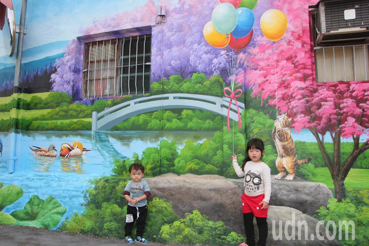 小朋友在彩繪牆前拍照,也融入畫作中。記者林宛諭/攝影