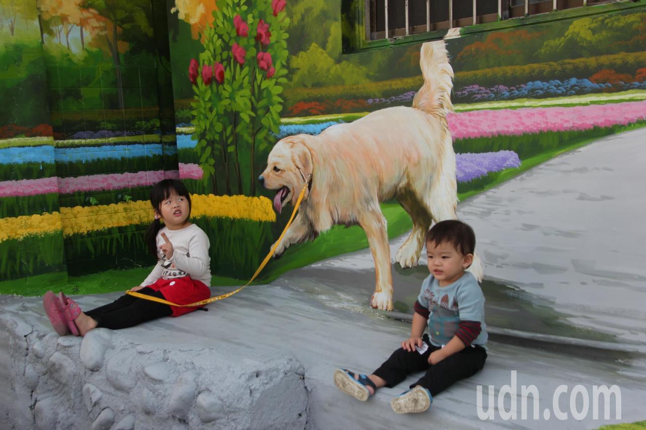「狗狗你要做什麼啊?」小朋友在彩繪牆前拍照,讓人會心一笑。記者林宛諭/攝影