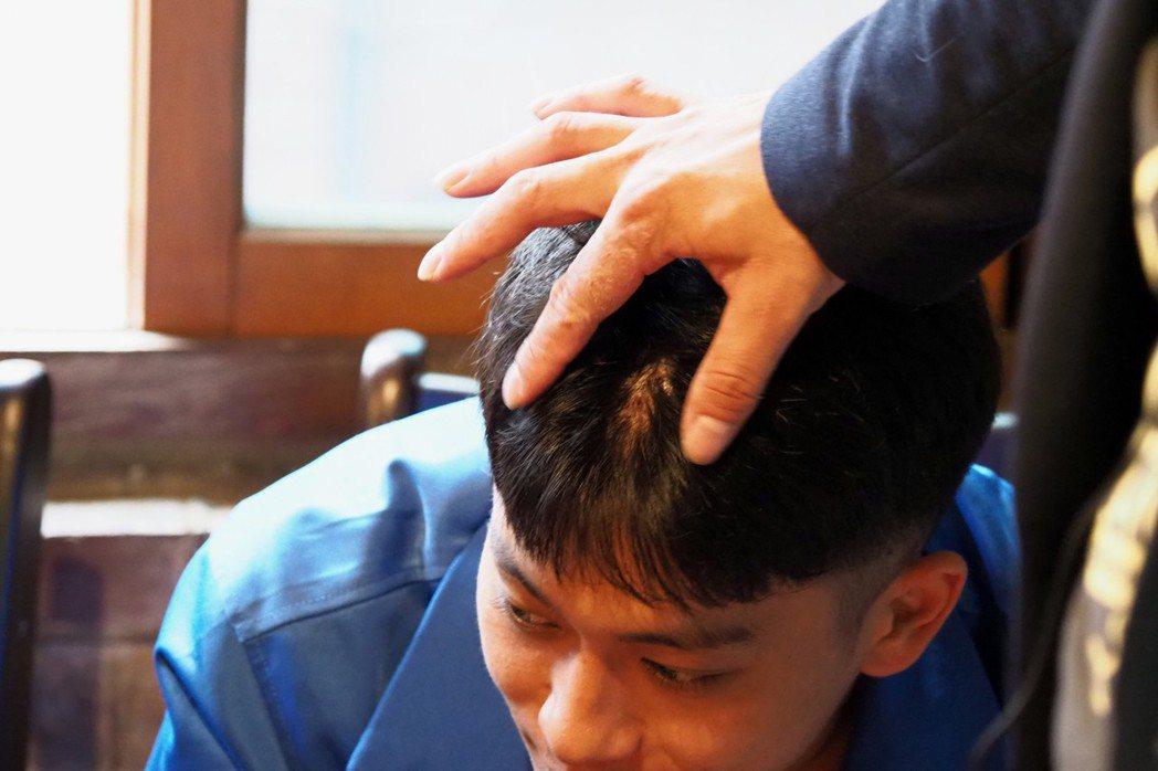 長時間操持法器,陳建宇的前額頂已出現乩童常見的傷口。 攝影/許伯崧