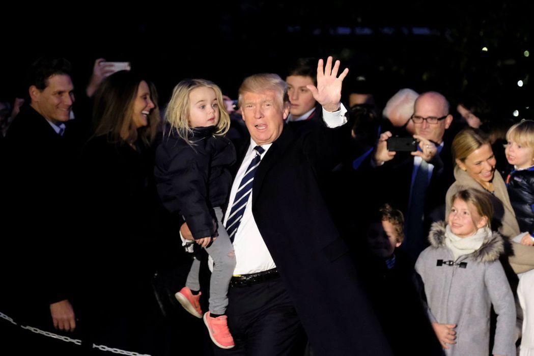 「通俄門」暫傷不了川普,他自紐約返回白宮時,抱著孫女向媒體打招呼。(路透)