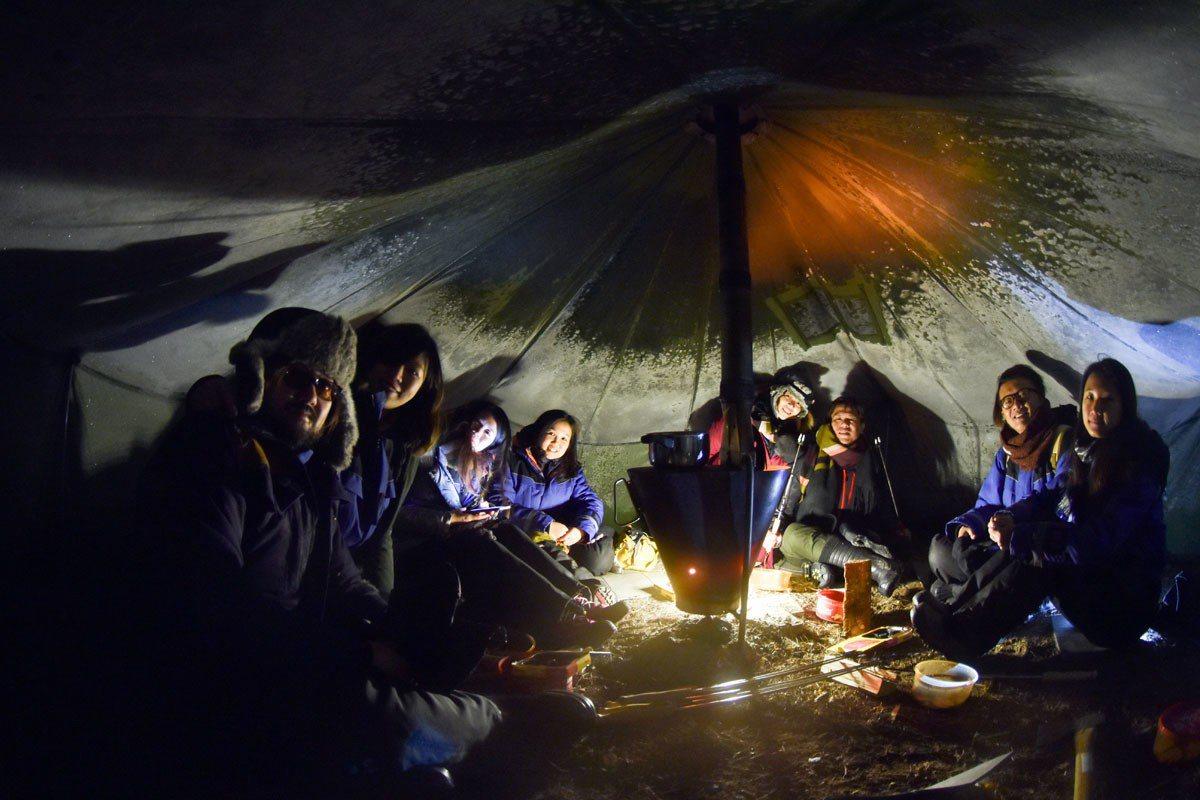 極光攝影團的成員在帳蓬內升火取暖,等待極光出現。