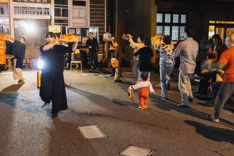 在小鎮開起了歡迎會,當地居民教外國遊客跳花笠舞,大家圍成圓圈歡笑前進。