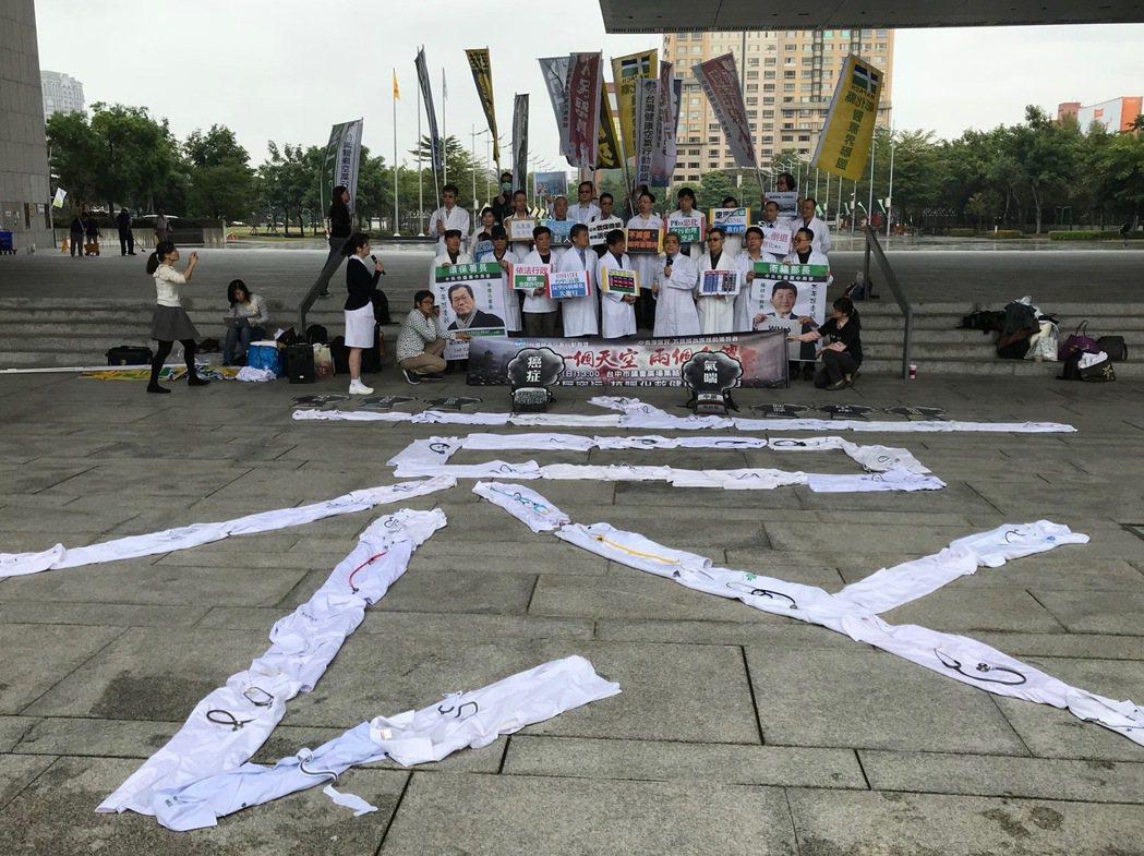 中台灣醫師團今早到中市府,脫下白袍排成「哀」字,抗議空汙嚴重。記者洪敬浤/攝影