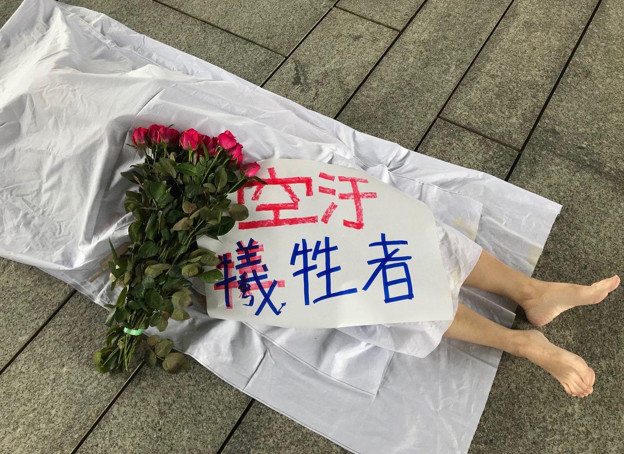 抗議空汙,環團今扮演「空汙犧牲者」,躺在中市府廣場頭蓋白布、獻上鮮花,為民眾健康...
