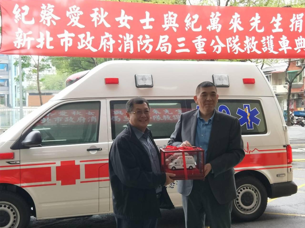 市民紀金財(左)以母親的名義捐贈救護車,由新北市消防局長黃德清(右)代表受贈。 ...