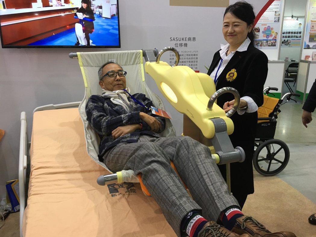 台灣醫療科技展中的新光醫院展區,展示病患位移機,在專人示範下,能在病床及輪椅間輕...