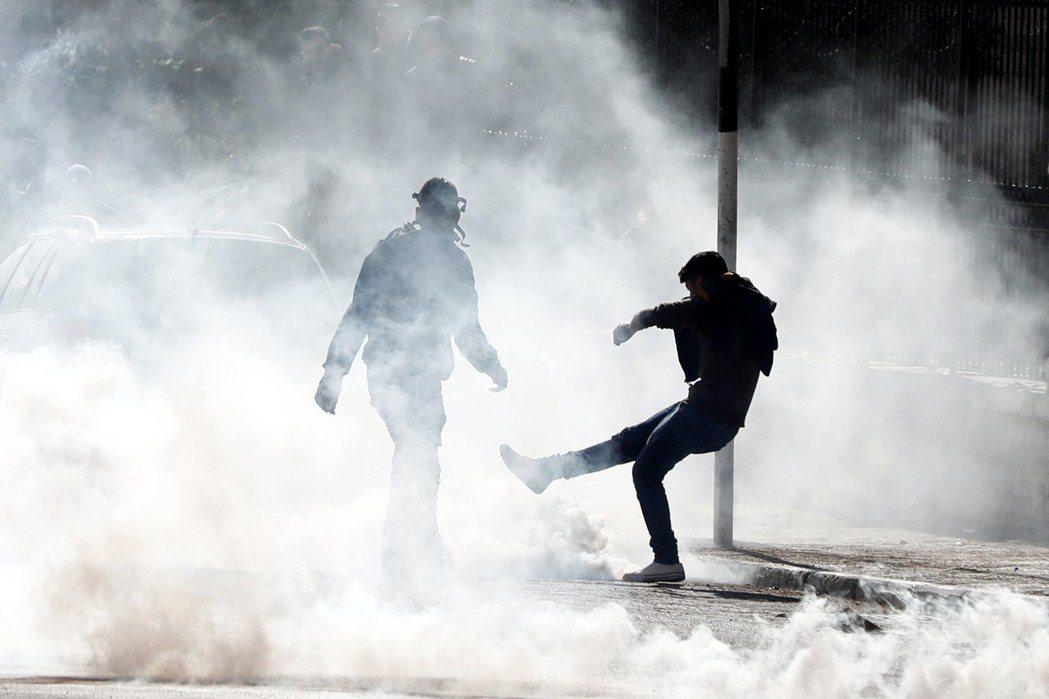 一名巴勒斯坦男子踢開以色列軍隊發射的催淚瓦斯。歐新社