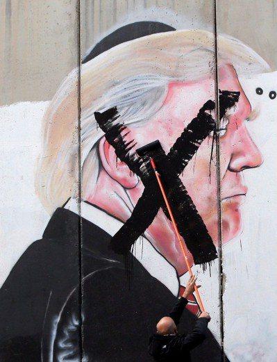 一名巴勒斯坦男子七日在約旦河西岸城市伯利恆,將畫在以色列所築圍牆上的美國總統川普...