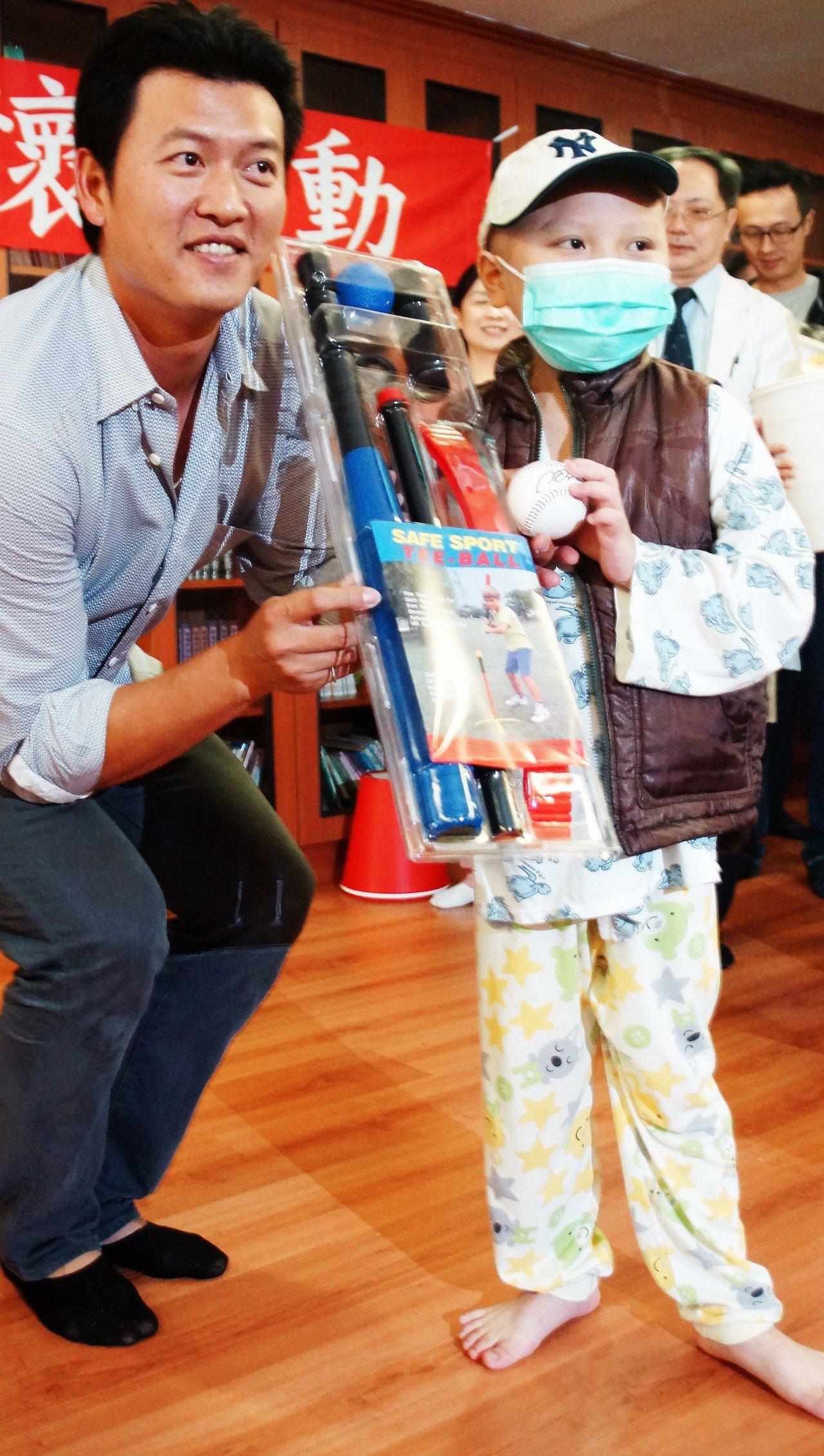 旅美球星王建民(左)8日至高雄長庚醫院關懷病童,與病童互動並致贈簽名球等禮物。 ...