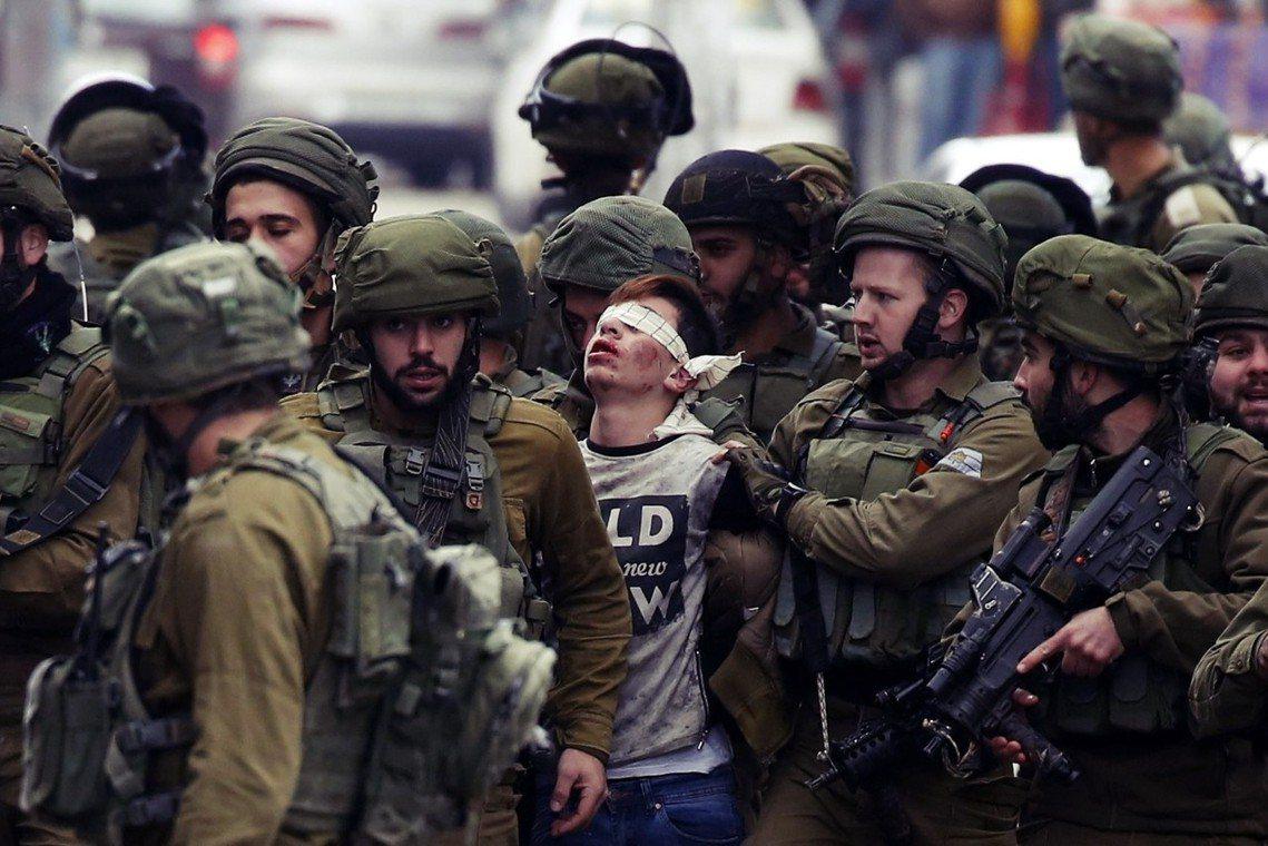 希伯崙的以色列軍隊整逮捕一名示威的巴勒斯坦少年。 圖/歐新社
