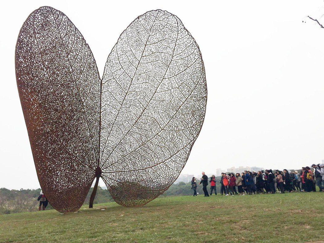 巨型公共藝術品「葉子」(LEAF),紅鏽色的葉子立在一片綠意之中,雙瓣形的葉片像...