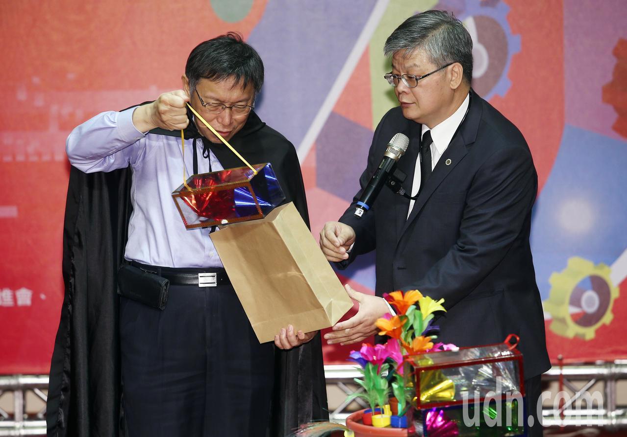 化身魔法師的柯市長(左),從空紙袋中拿出內藏「無盡祝福」布幕的塑膠盒,獲得在場熱...
