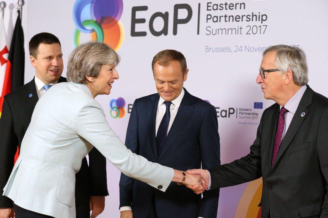 英國首相梅伊(左前)和歐盟執委會主席容克(右)會談前握手。歐新社