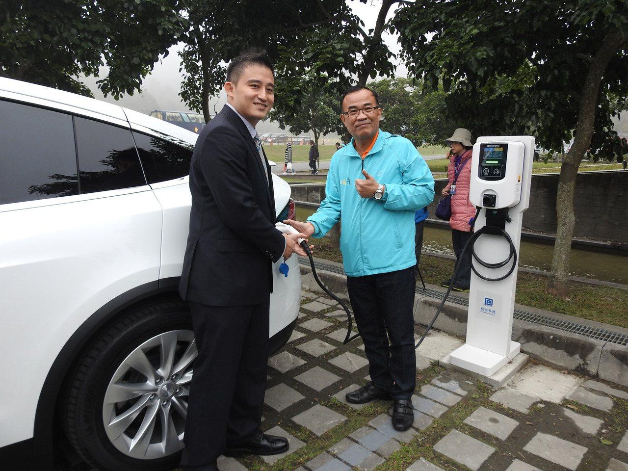 日管處處長洪維新(右)今和飛宏科技總經理林飛宏(左)試用電動車充電系統。記者賴香...