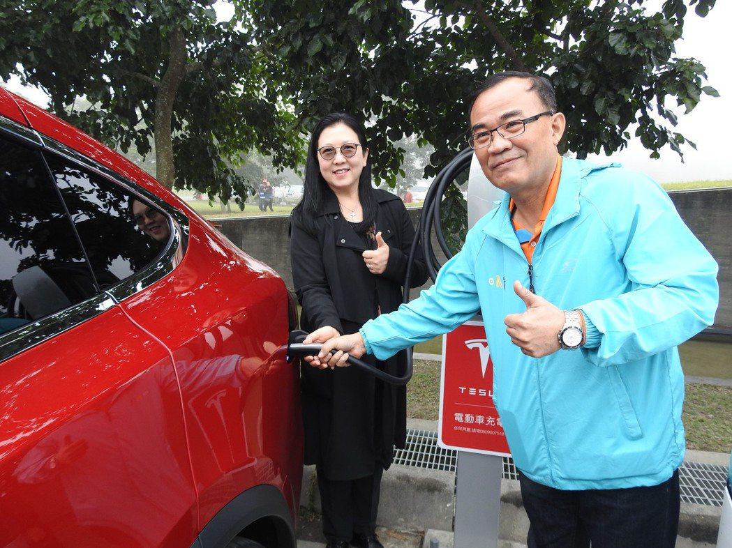 日管處處長洪維新(右)今和特斯拉台港澳市場總監范菁怡(左)試用電動車充電系統。記...
