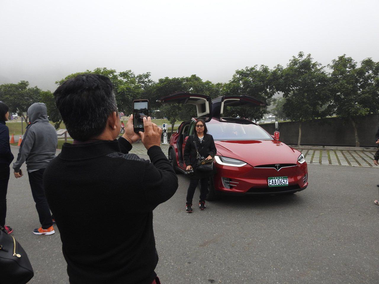 民眾今在日月潭向山遊客中心看見「特斯拉」紛紛拿起手機搶拍,甚至合影留念。記者賴香...