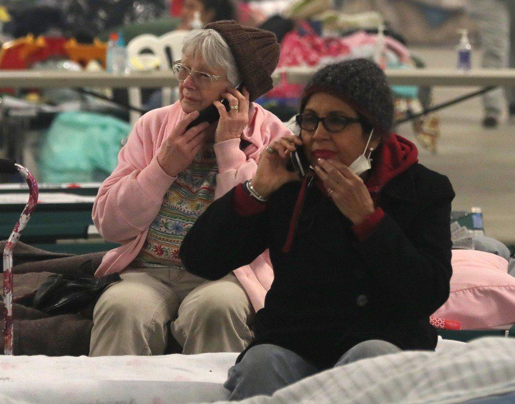 撤離到緊急避難區的老人,急著打電話聯繫家人。 (歐新社)