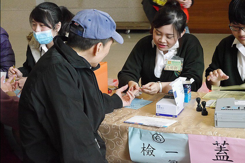 學生協助居民測量血糖。 長庚科大/提供