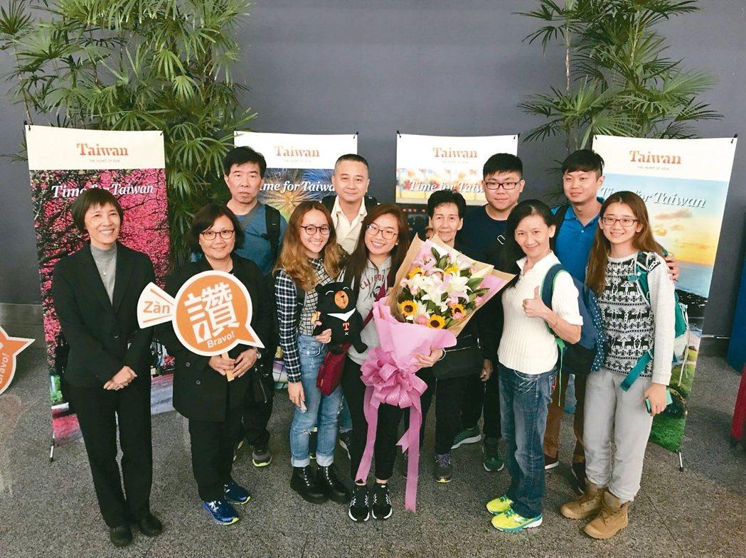 來台旅客中午正式突破千萬大關,是首次來台的23歲新加坡女生(捧花者),意外獲得觀光局贈禮相當開心。 觀光局/提供