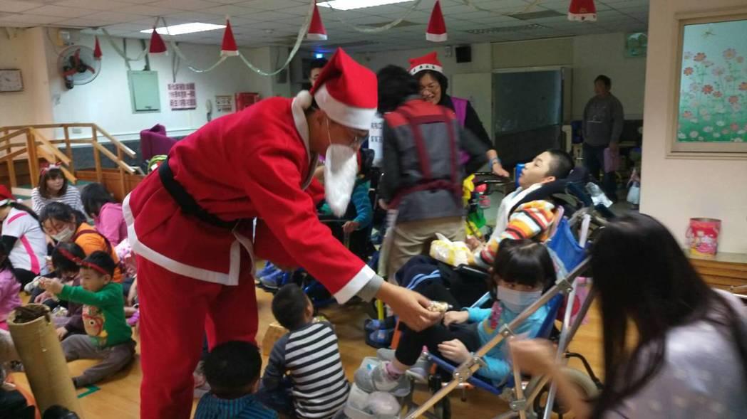 彰化縣和仁志工隊隊員扮演耶誕老人送禮物給發展學園兒童。圖/家扶提供