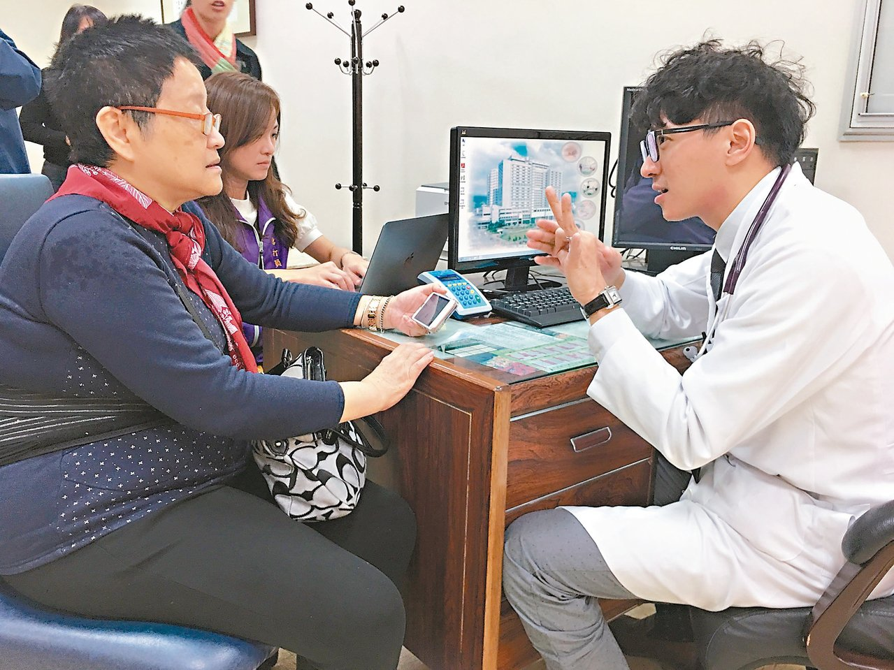 聽打員(左後)協助聽障密斯余讓瑩(左前)看診。 記者鄧桂芬/攝影