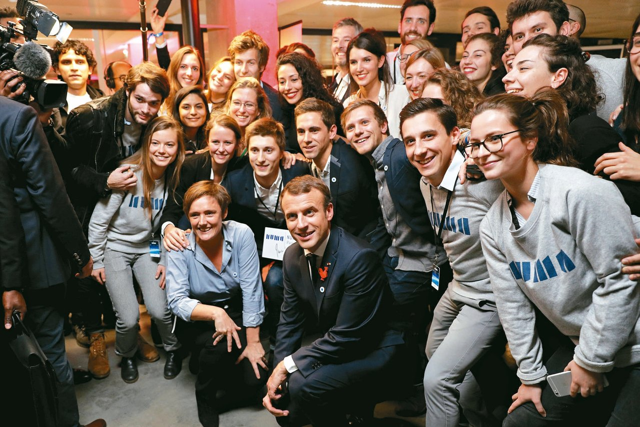 法國總統馬克宏(中)在巴黎與獲得「讓地球再次偉大」計畫贊助的科學家合影。 路透