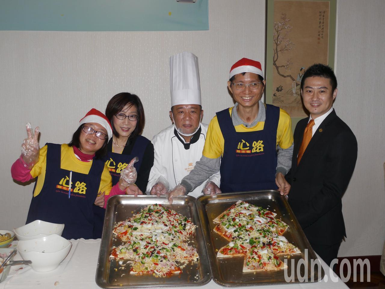 高市議會議長康裕成(左2)陪伴心路青年製作披薩,眾人合力完成聖誕樹造型的大披薩。...
