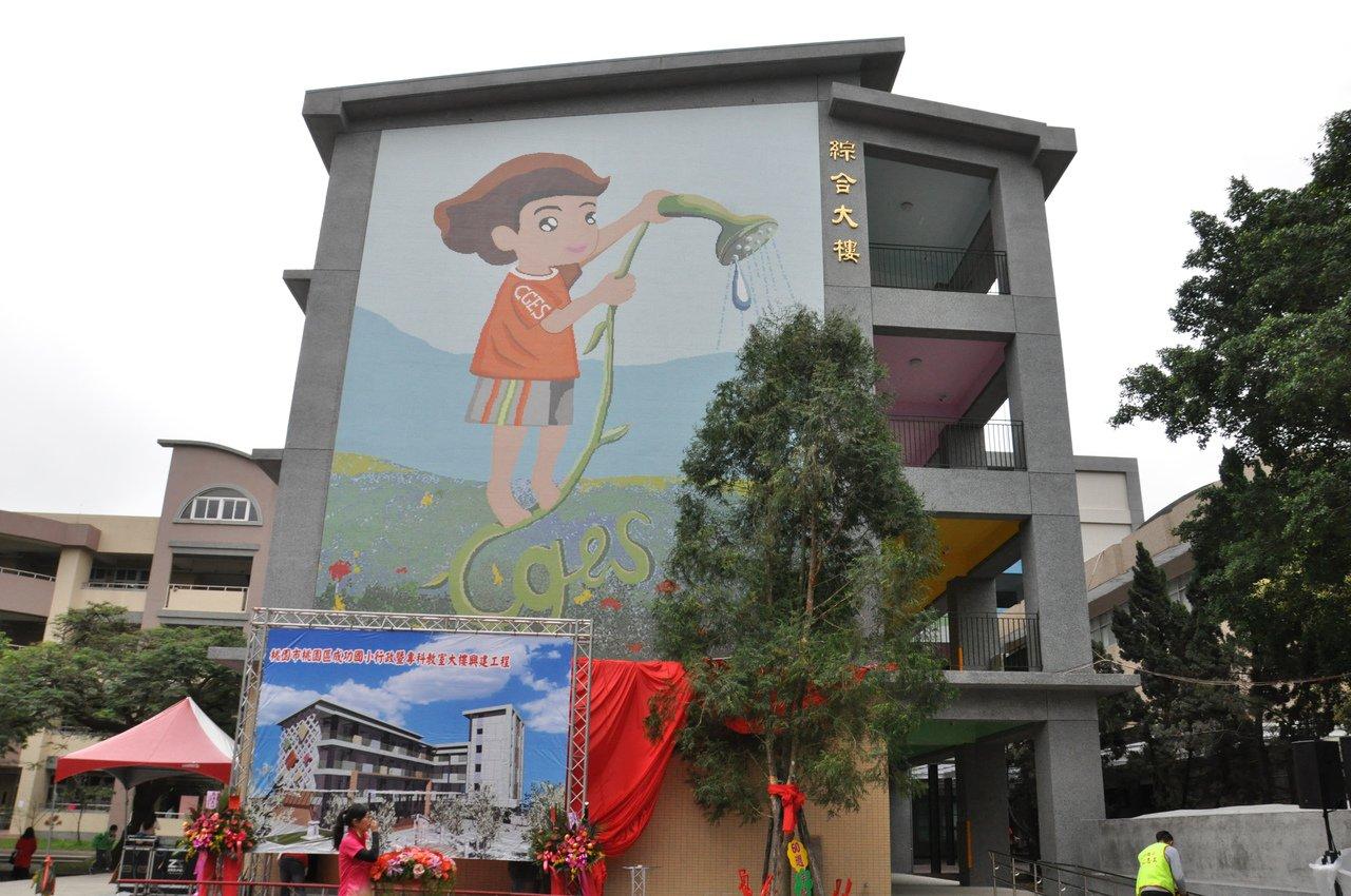 成功國小新的綜合大樓牆面以馬賽克彩磚拼貼,一旁則栽種60周年紀念樹肖楠,圖像設計...