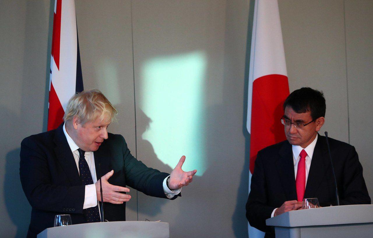 英國外相強森(左)14日在倫敦國家海事博物館與日本外務大臣河野太郎舉辦共同記者會...