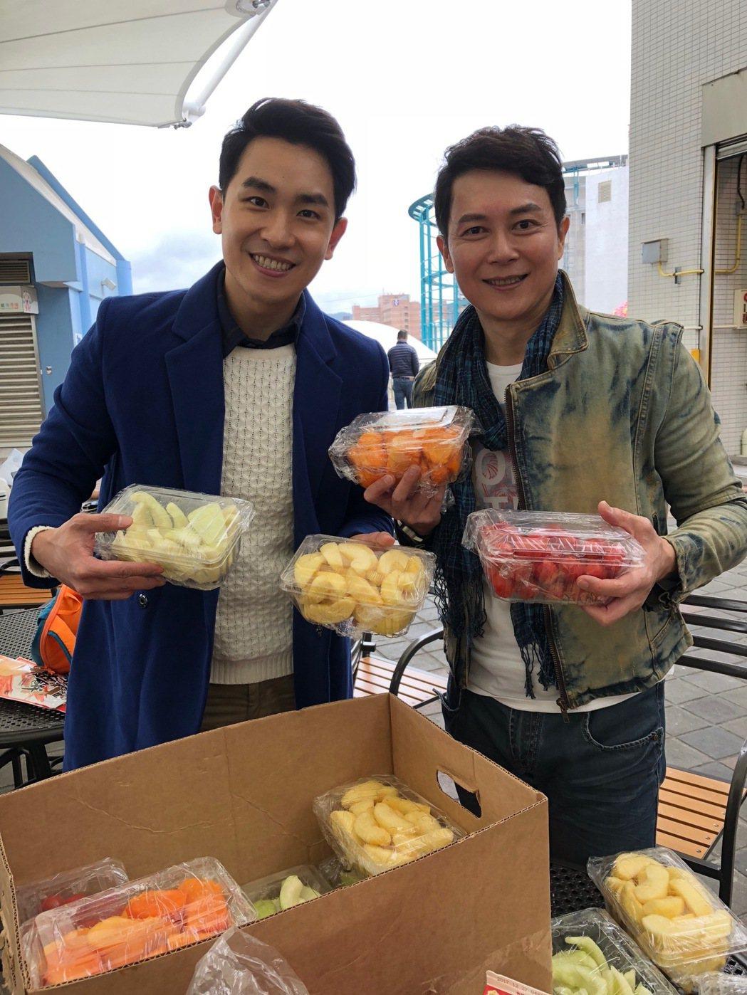 陳謙文(左)、王燦捧自家賣的水果,分享給小朋友們。圖/民視提供