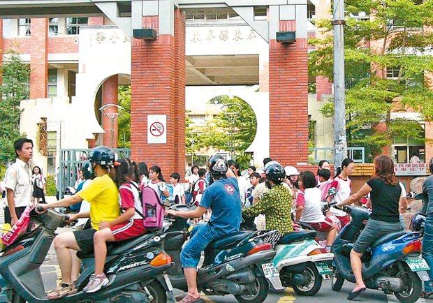 每到放學時刻,學校校門口常被接送家長們包圍,形成交通亂源。 報系資料照