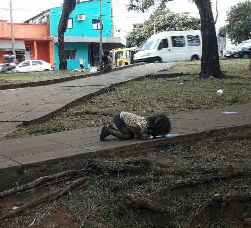 阿根廷一名小女孩因天熱口渴,趴在地上舔喝積水,英國「太陽」報(The Sun)以...